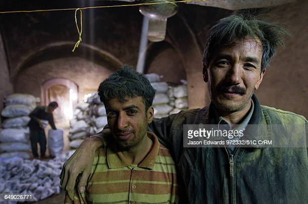 The exhausted faces of friends working in an ancient henna mill