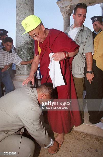 The exiled Tibetan spiritual leader the Dalai Lama is helped to remove his shoes before entering the Dome of the Rock the third holiest site in Islam...