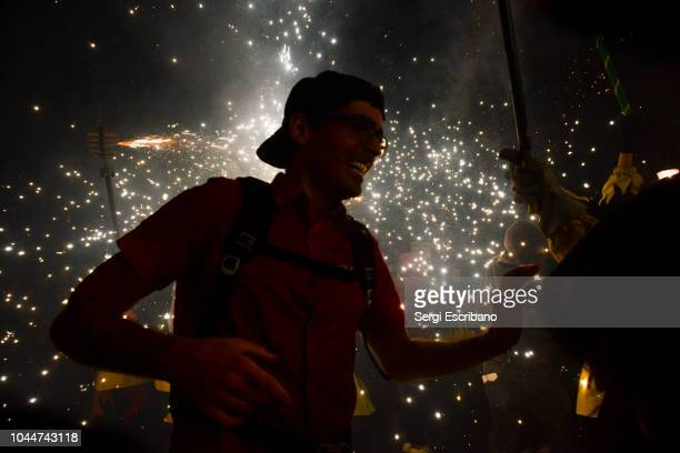 The explosion of a large firecracker impacts directly on a man standing still, during the traditional correfocs of La Mercè festivities in Barcelon