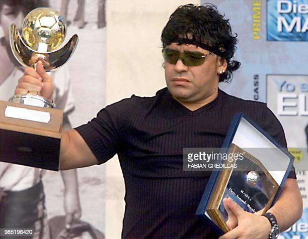 The exsoccer player Diego Maradona shows the prize which is awarded him as the best player of the world chozen by the FIFA internet inquiry in...
