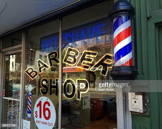 The exterior glass facade of a ground floor commercial storefront Barber Shop with a traditional barbers pole Park Slope Brooklyn NYC September 25...
