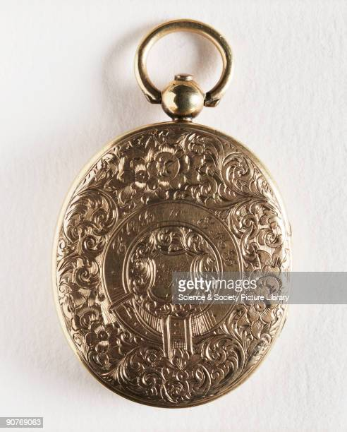 The exterior of a gold locket with intricate engraving of flowers and leaves and the dedication 'FCB to EMB Jan'y 5th 1855' made by an unknown...
