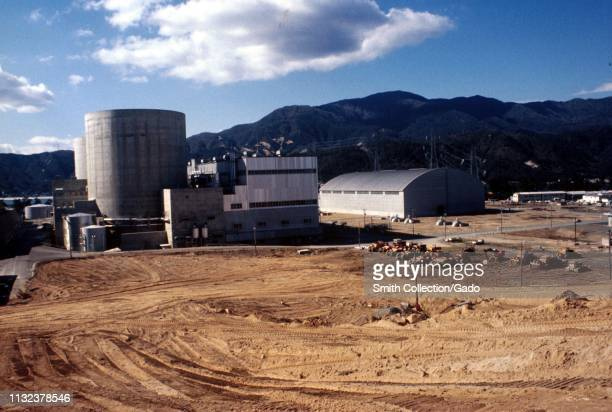 The exterior of Mihama Nuclear Power Plant, on a sunny day, with dirt and construction vehicles in the foreground, Mihama, Japan, 1975. Image...