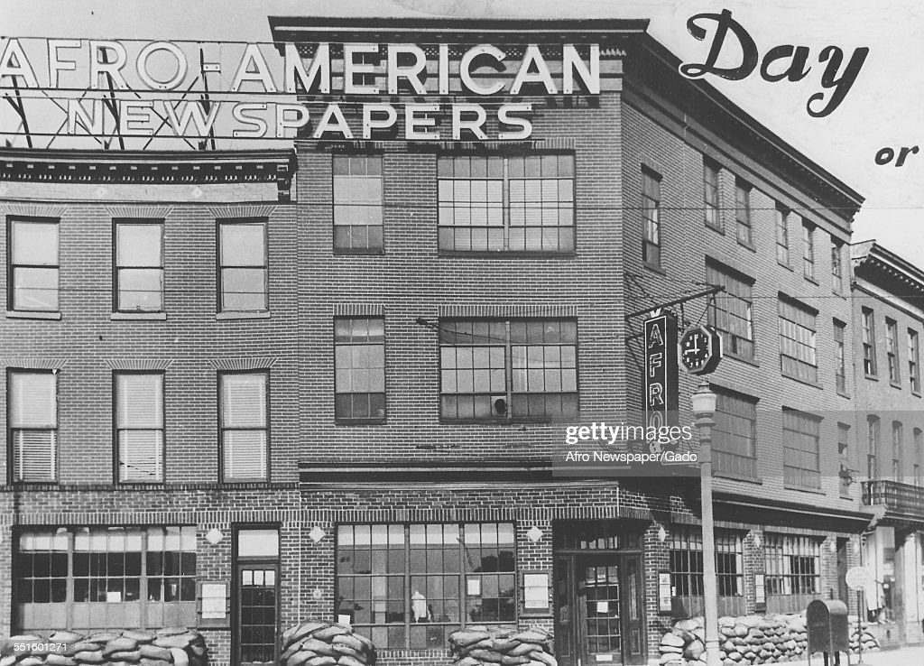 The exterior of the Afro American newspaper building, with a large sign, and sandbags piled up on the street, Baltimore, Maryland, 1935.