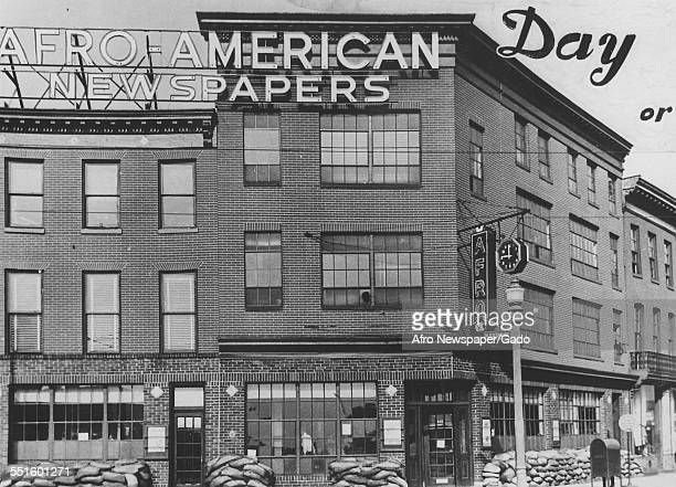 The exterior of the Afro American newspaper building with a large sign and sandbags piled up on the street Baltimore Maryland 1935