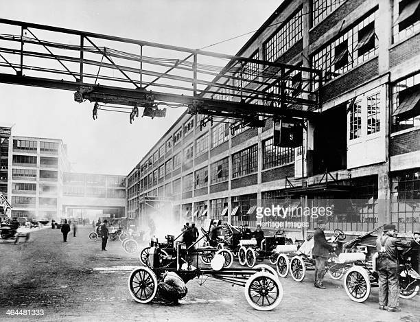 The exterior of the Model T factory 1914 Cars lined up along the factory wall with mechanics working on them