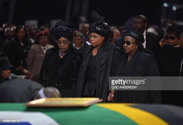 The exwife of Nelson Mandela and antiapartheid campaigner Winnie Mandela Madikizela and the widow of Nelson Mandela Graca Machel stand by the coffin...
