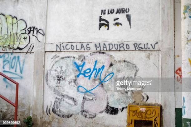 The eyes of Hugo Rafael Chávez Frías are painted on a wall above the name of his successor Nicolás Maduro Moros and the PSUV'nThe PSUV is the name of...