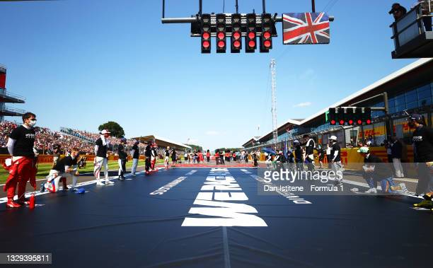 The F1 drivers stand and kneel on the grid as part of the We Race As One gesture before the F1 Grand Prix of Great Britain at Silverstone on July 18,...