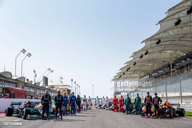 The F1 drivers stand on the grid with their cars during Day One of F1 Testing at Bahrain International Circuit on March 12, 2021 in Bahrain, Bahrain.