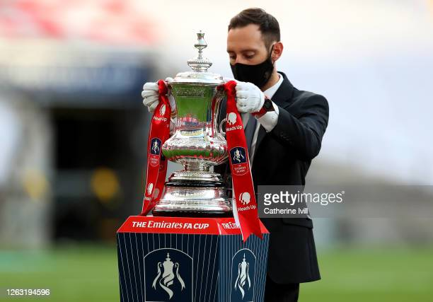 The FA Cup Trophy is prepared by a member of staff wearing a face mask and PPE during the Heads Up FA Cup Final match between Arsenal and Chelsea at...