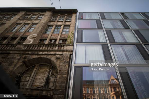 The facade of an old building is pictured next to the facade of a newly constructed building on April 24 2019 in Berlin Germany