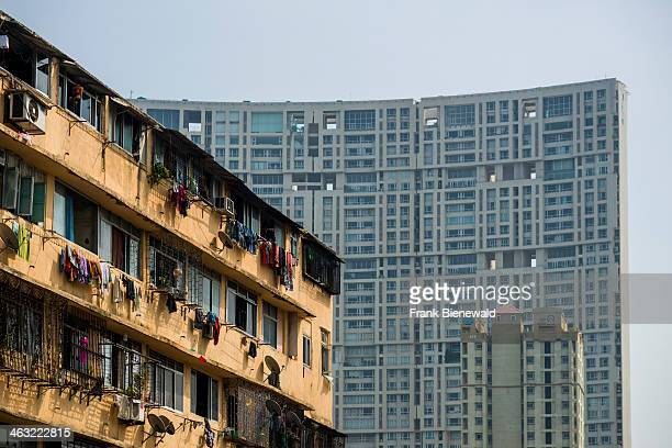The facades of a big apartment buildings with the windows of many flats typical homes of working class Indians