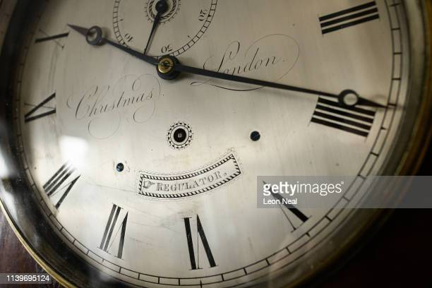 The face of a Christmas London regulator is seen as Duncan Clements of Pendulum of Mayfair antique clock specialists carries out the summertime...