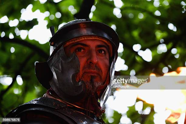 The face of a Roman soldier is illuminated by a flaming torch as he takes part in an evening patrol during the Hadrian's Wall Live event at...