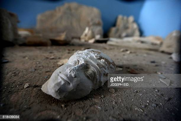 The face of a statue lies on the ground at the destroyed museum in the ancient Syrian city of Palmyra on March 31 2016 Syrian troops backed by...
