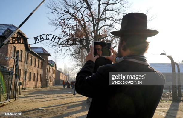 TOPSHOT The face of a visitor is reflected on the screen of his phone as he takes a picture of the main entrance at the Auschwitz German Nazi death...