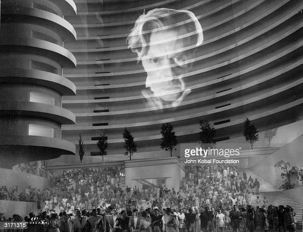 The face of English actor Ernest Thesiger is projected onto the side of a building in the futuristic drama 'Things to Come' directed by William...