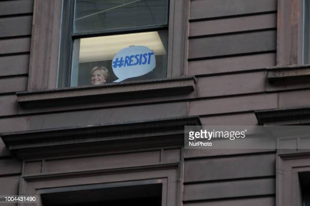 The face of Hillary Clinton on a cardboard cutout looks down on protestors in Handsmaids Tale attire gather outside a fundraiser attended by Vice...