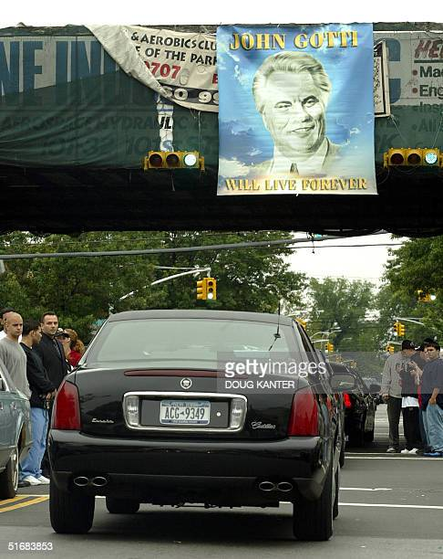 The face of John Gotti beams down from a sign near the Bergin Hunt and Fish Club in Queens New York 15 June 2002 as his funeral procession drives by...