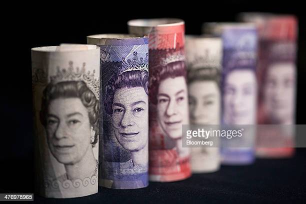 The face of Queen Elizabeth II is seen on rolled ten twenty and fifty pound sterling banknotes in this arranged photograph taken in London UK on...
