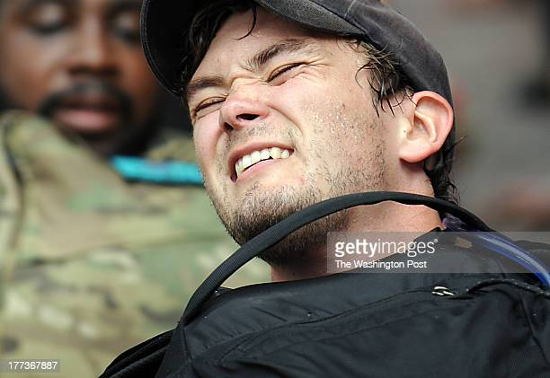 The face of Washington Post reporter TRees Shapiro suggests pain while he is forced to crawl on his back with a brickfilled backpack on his belly...