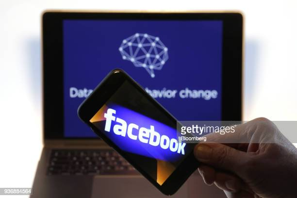 The Facebook Inc logo is displayed on an Apple Inc iPhone against the backdrop of the Twitter Inc banner image from Cambridge Analytica's verified...