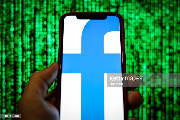 The Facebook logo is seen displayed on a mobile device in front of a screen with data in this photo illustration in Warsaw Poland on March 19 2019