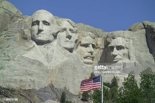 The faces of American Presidents George Washington Thomas Jefferson Theodore Roosevelt e Abraham Lincoln carved in the granite American flag in the...