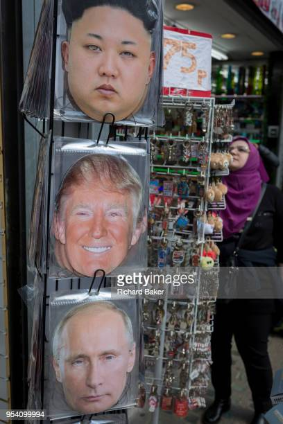 The faces of North Korean leader Kim Jongun a smiling US President Donald Trump and Russian President Vladimir Putin appear on face masks outside a...