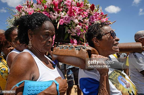 The faithful carry the image of Our Lady of Boa Viagem from a boat to the Boa Viagem beach during the Bom Jesus dos Navegantes festival in Salvador...