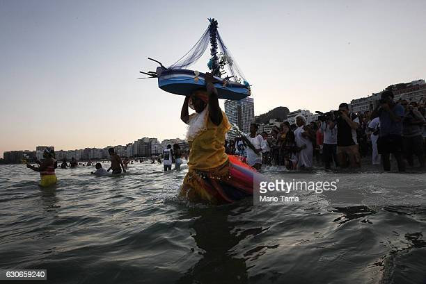 The faithful enter the ocean during a ceremony honoring Iemanja, Goddess of the Sea, as part of traditional New Year's celebrations on the sands of...