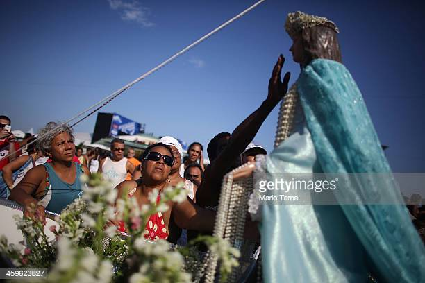 The faithful gather and worship at the Iemanja statue during a ceremony honoring Iemanja, Goddess of the Sea, as part of traditional New Year's...