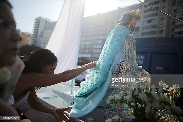 The faithful gather and worship at the Iemanja statue during a ceremony honoring Iemanja Goddess of the Sea as part of traditional New Year's...