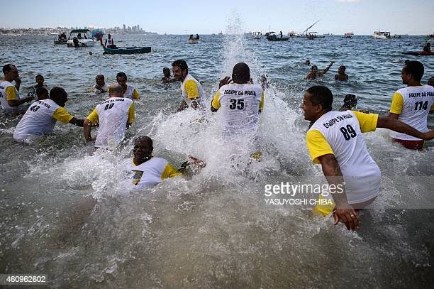 The faithful play with water as they wait for the arrival of the image of Bom Jesus dos Navegantes to the Boa Viagem beach in Salvador Bahía Brazil...