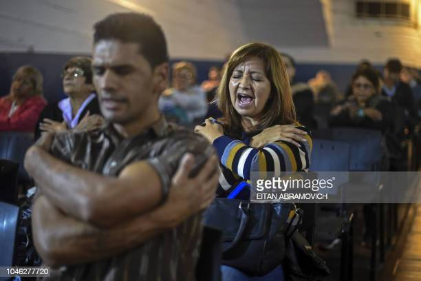The faithful pray during a meeting at Pastor Gimenez's Church located in the former Roca cinema of Almagro neighborhood in Buenos Aires Argentina on...