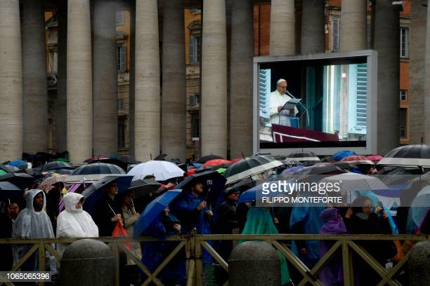 The faithful protect themselves from the rain with unbrellas as Pope Francis delivers his message during the weekly Angelus prayer on November 25...
