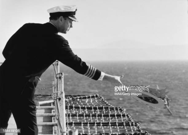 The Falklands Conflict April June 1982 A naval officer laying a wreath into the water during a memorial service held on board the Cunard liner...