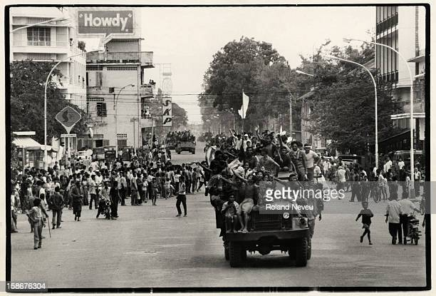 The fall of Phnom Penh. A convoy of trucks and armoured personnel carriers commandered by the victorious Khmer Rouge drives through the city center...