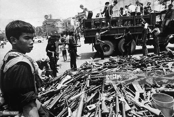 The fall of Phnom Penh. Throughout the day, Khmer Rouge regular forces dressed in black collected weapons left behind by Lon Nol soldiers who had...