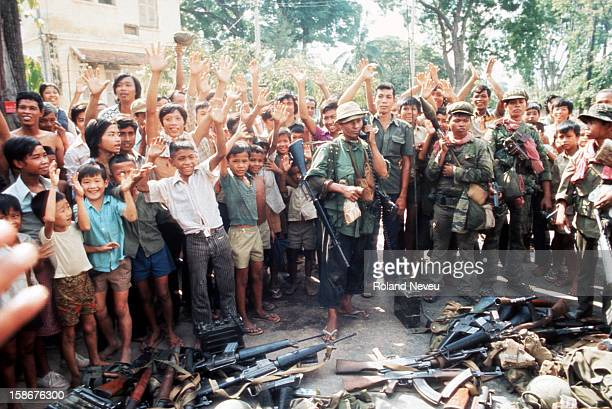 The fall of Phnom Penh. Victorious Khmer Rouge soldiers are cheered on by a crowd of youngsters, opposite the French embassy..