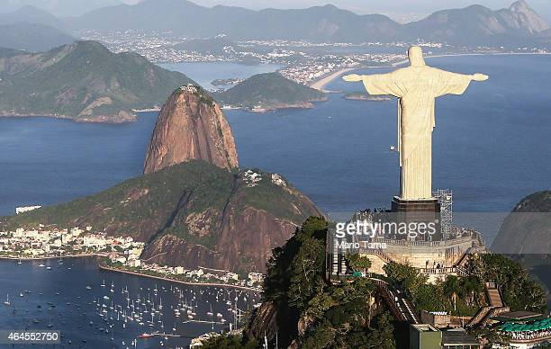 The famed Christ the Redeemer statue stands above Guanabara Bay in an aerial view on February 24 2015 in Rio de Janeiro Brazil The Art Deco statue is...