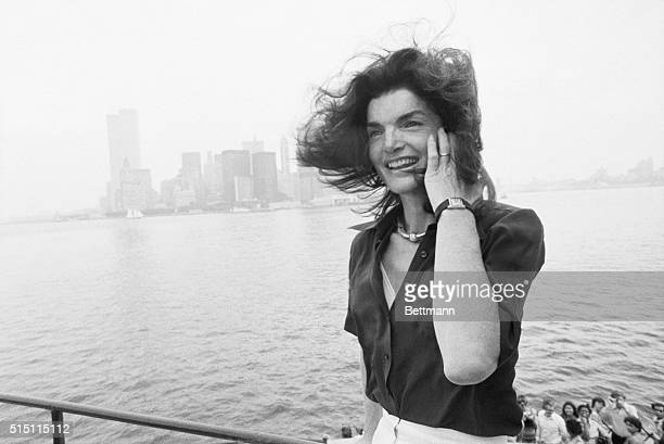 The familiar towers of lower Manhattan and the notunknown physiognomy of Jacqueline Kennedy Onassis can be made out in New York Harbor as she returns...