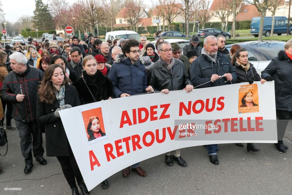 The familly of Estelle Mouzin, including Eric Mouzin (C), the father, hold a banner reading help us find Estelle during a silent march in Guermantes, near Paris, fifteen years after the disappearance of the nine-year old girl. Estelle Mouzin disappeared on January 9, 2003 in Guermantes village some 26 kilometers from Paris.