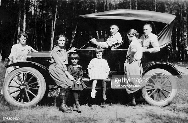 The family gather in and on the running board of their automobile