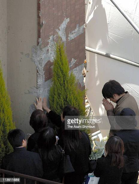 The family members and relatives of the victims of 107 people killed derailment in 2005 touch the wall of the apartment which the train plunged into...