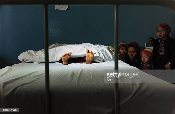 The family of a five year old Afghan girl that was allegedly raped by a 22 year old man looks on as she lies in a hospital bed in Kaldar district of...