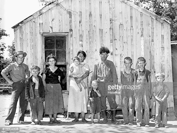 The family of an agricultural day laborer a former oil worker and coal miner in front of their two room home in McIntosh County Oklahoma June 1939