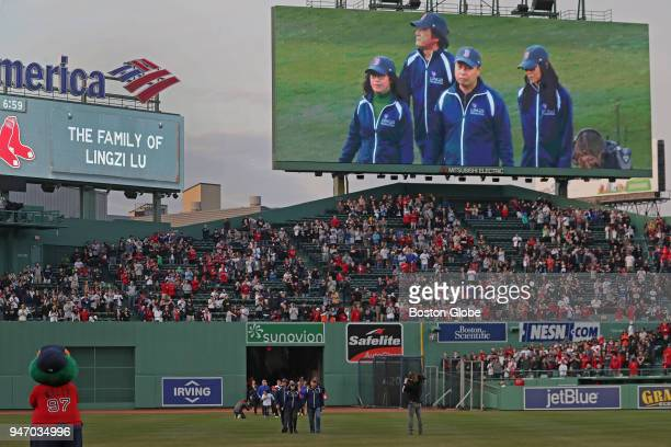 The family of Boston Marathon bombing victim Lingzi Lu stand on the field during a pregame ceremony honoring victims survivors and heroes of the...