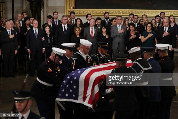The family of former US President George HW Bush stand as his flagdraped casket is carried into the US Capitol Rotunda during an arrival ceremony...